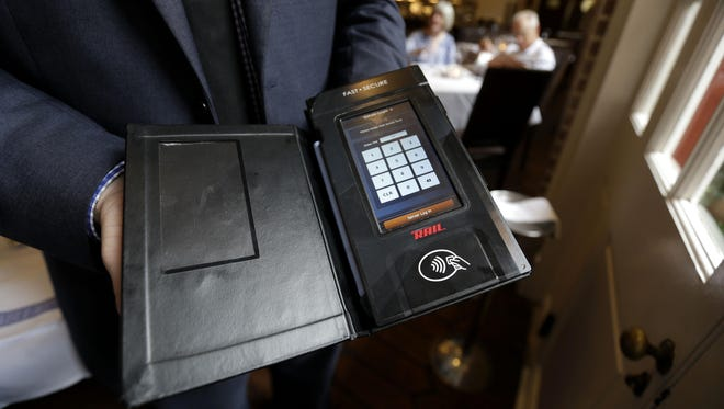 Service Manager Morgan Mallory holds a Rail table side credit card processing device at Tableau, a Dickie Brennan & Co. restaurant in New Orleans.