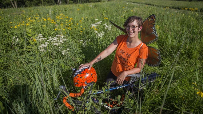 RAGBRAI rider Kelly Guilbeau of Grinnell plans to hand out milkweed seeds along the ride to help create more monarch butterfly habitats. Here she stands with her bike at the Conrad Environmental Research Area near Kellogg, Iowa.