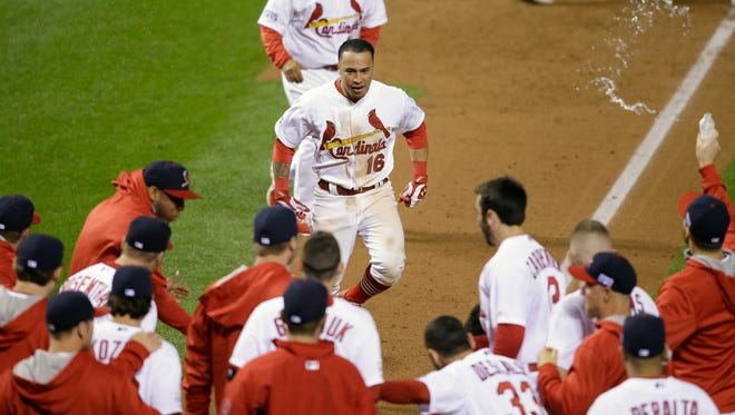 The Cardinals' Kolten Wong celebrates after hitting a walk off home run during the ninth inning in Game 2 of the NLCS against the San Francisco Giants on Sunday.