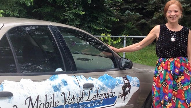 Kimberly McDole stands next to the vehicle she uses for making house calls for her mobile veterinary service.