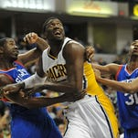 Pacers center Roy Hibbert (middle) gets tangled with Philadelphia 76ers players. March 17, 2014