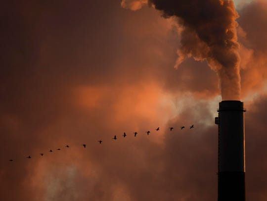 A flock of geese fly past a smokestack at the Jeffery