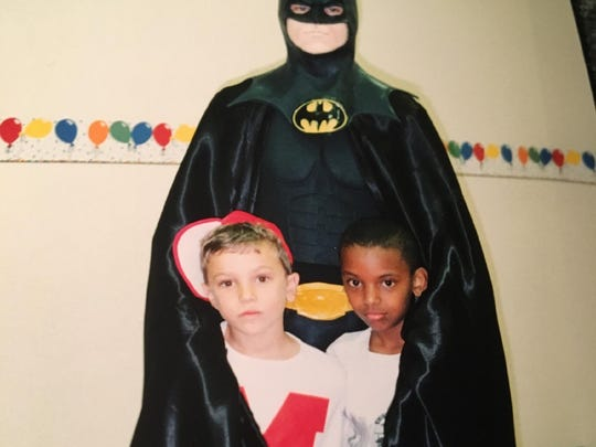 """Andrew Taylor and James Green take a photo with """"Batman"""" at a birthday party for Andrew in the early '90s."""