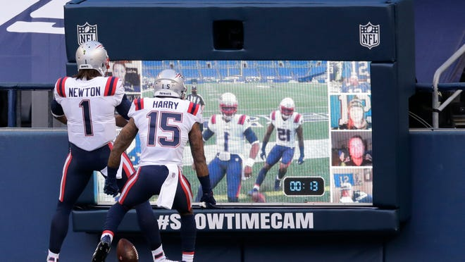 New England Patriots quarterback Cam Newton (1) and wide receiver N'Keal Harry (15) celebrate in front of a two-way video display after Newton scored a touchdown against the Seattle Seahawks during the first half of an NFL football game, Sunday, Sept. 20, 2020, in Seattle.