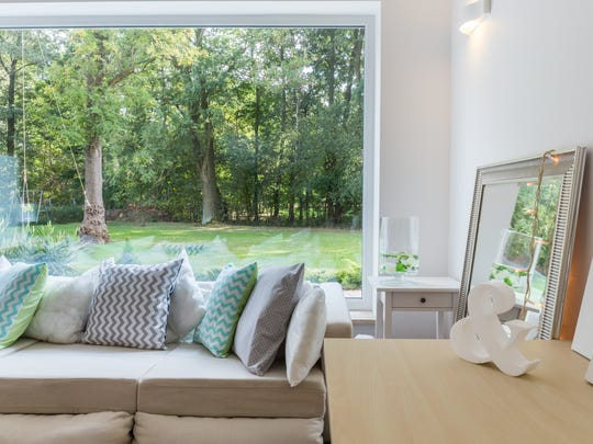 A large mirror and windows with minimal treatments