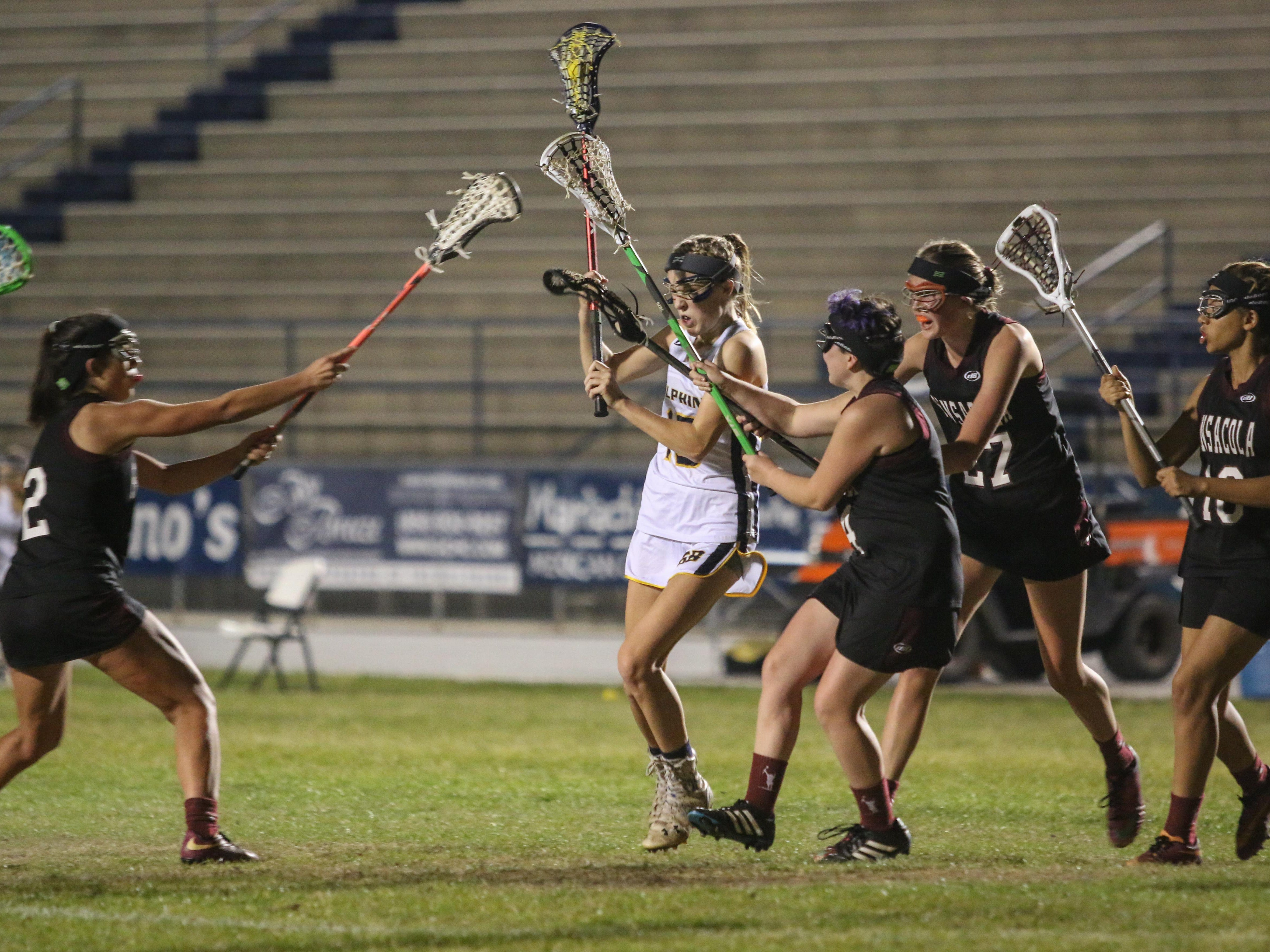 Gulf Breeze's Francis Williams (15) fights her way through the Pensacola players on her way to the goal Thursday night during the District 1-1A girls lacrosse championship game at Gulf Breeze High School.