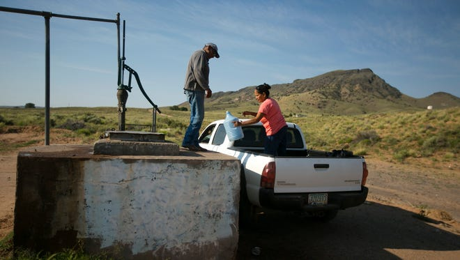Levi Biggambler, 70, and his wife, Linda, 63, fill up water containers with fresh drinking water at a pump about five miles from their home outside of Teesto, Ariz.