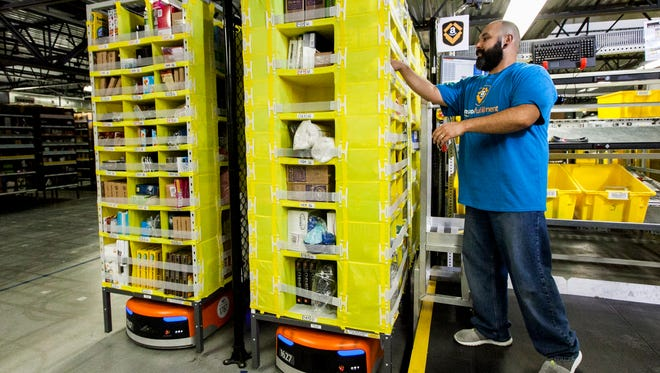 An Amazon employee picks items to package brought to him by a Kiva Systems robot (the orange unit below the shelving).