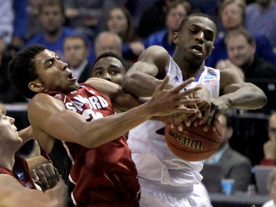Kansas' Andrew Wiggins, right, and Stanford's Josh Huestis reach for a rebound during the first half of a third-round game of the NCAA college basketball tournament Sunday, March 23, 2014, in St. Louis. (AP Photo/Jeff Roberson)