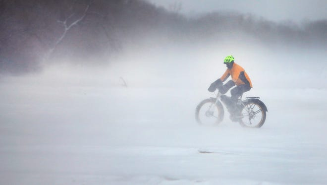 Avid cyclist Brian Managan braves cold temperatures and a howling wind off of Lake Ontario to ride his Surly Pugsley fat bike on the Durand Eastman Beach.