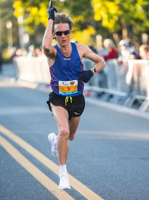 Parker Stinson, 25, from Boulder, Colorado crosses the finish line as the first male runner with a time of 1:03:34.3 during the Naples Daily News Half Marathon on Sunday.