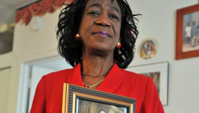 In this 2009 photo, President Obama's aunt, Zeituni Onyango, poses in her home in Boston with a framed photograph of Obama and herself, when he was an Illinois state senator.  Onyango, whose status as an illegal immigrant was revealed days before Obama was elected in 2008, died Tuesday.