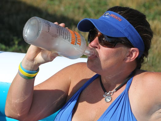 Melissa Hensley , of New Richmond, cools off in a pool and drinks vodka at the Ponderosa Campground at Kentucky Speedway where fans are watching a triple-header race weekend.