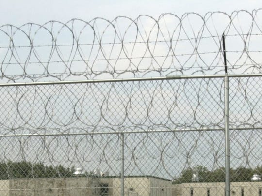 Two fences topped with razor wire surround the Southern State Correctional Facility in Springfield.