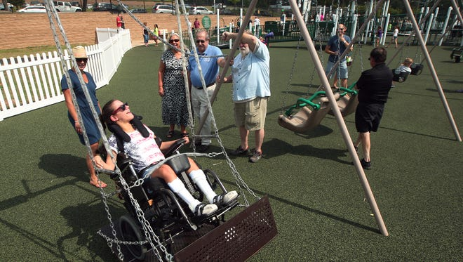 19-year-old Mary Rita Tortorello of Randolph gets a push on the all access swing from her mom Maryanne as the Morris County Park Commission celebrates the grand opening of the Jets Play60 All Access Playground at Central Park of Morris County in Parsippany, September 6, 2014, Parsippany, NJ. Photo by Bob Karp