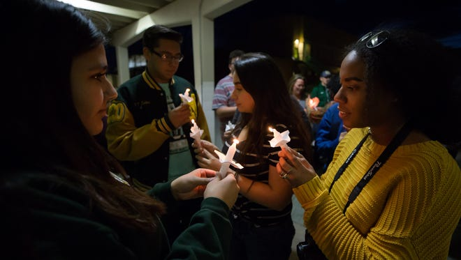 Reyana Florez, left, 14 and Makana Johnson, 16, light their candles before the start of the candlelight vigil to remember the victims of the Marjory Stoneman Douglas High School in Parkland, Florida at Mayfield High School on February 21, 2018.