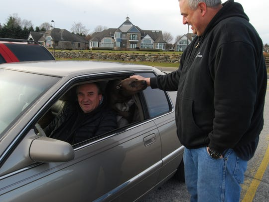 Ed Hunt says hello to Mike Mellick and Mellick's dogs, Minnie and Max, on Saturday at Thomas Edison Parkway.