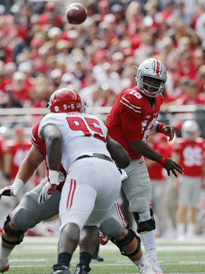 Ohio State quarterback J.T. Barrett throws a pass over the Rutgers defense during the second half on Saturday.
