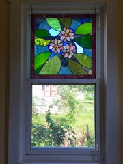 Stained glass made by Betsy Cook adorns her home's windows and even the doors.