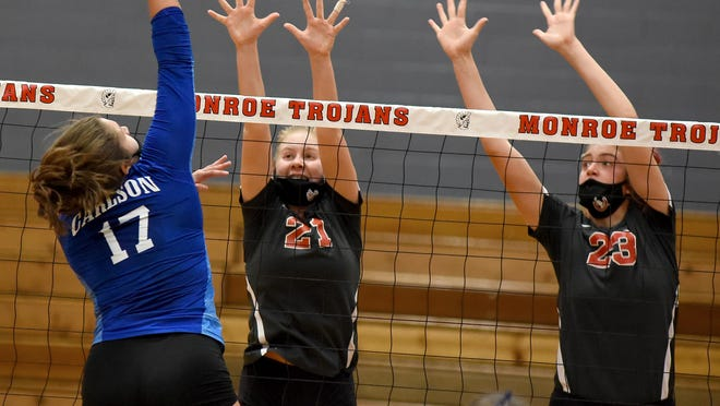 Bedford's Caris Cross and Sophia Gray go up to block a hit from Allyson Dillon of Gibraltar Carlson during the Division 1 District final at Monroe last week.