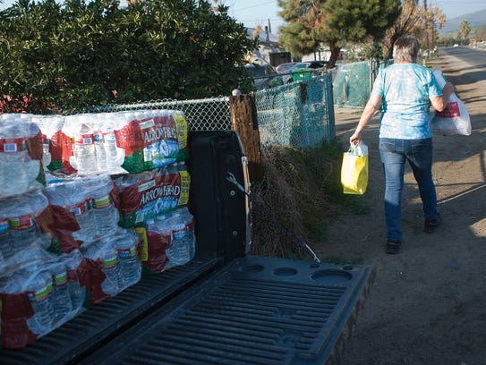 Donna Johnson delivers drinking water, plastic silverware,