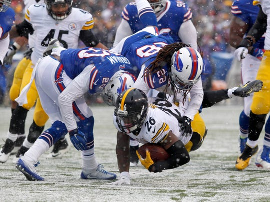 Ronald Darby (28) and Corey Graham (20) tackle Steelers running back Le'Veon Bell during a game in December. Darby and Graham are now with the Eagles.