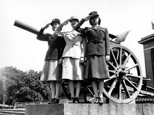 This May 22, 1942 file photo shows U.S. Army women saluting as they fashion the official uniforms of the Women's Army Auxiliary Corps (WAACS) for the first time in Washington, D.C.