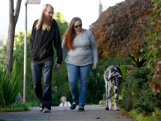 Kaity and Tim Evans walk with their Great Dane Ziggy, 11, on Nov. 17, 2016 near their apartment in Oakland, Calif.. They give Ziggy a Treatibles cannabis pill each day to help his arthritis.