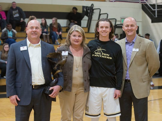 Brian and Kathy Haugen, and Jeff Jourdan, from the Taylor Foundation, present Josiah Pool with the Taylor Haugen Award before the start of Tuesday night's District 1-7A basketball game in Milton. It is Santa Rosa County's first time receiving the honor.