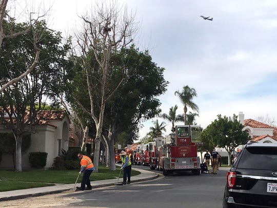 Crews clean up near where a helicopter crashed into a house in Newport Beach, Calif., Tuesday, Jan. 30, 2018. The four-seat Robinson R44 crashed shortly after takeoff at John Wayne Airport, killing several people and injuring a few others. (AP Photo/Amy Taxin)