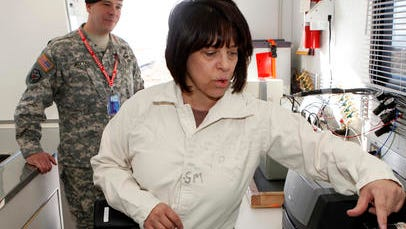 FILE -In this Jan. 21, 2010, file photo, Debra Michaels, Chemical Operations Manager demonstrates a gas chromatograph inside a mobile testing lab at the Army's Pueblo Chemical Storage facility in Pueblo, Colo. The lab is used to test the air for leaking mustard agent. Depot commander Lt. Col. Robert C. Wittig looks on at left. On Wednesday, Aug. 31, 2016, the U.S. Army said that it plans to start operating a $4.5 billion plant next week that will destroy the nation's largest remaining stockpile of mustard agent, complying with an international treaty banning chemical weapons. (AP Photo/Ed Andrieski, File)