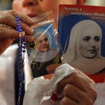 A woman holds up religious articles related to Mother Laura Montoya in the cathedral in Bogota, Colombia in 2013. The planned debut Wednesday of a telenovela dramatizing the life of Montoya, Colombia's only Roman Catholic saint, is shrouded in controversy after devotees filed a lawsuit seeking to correct what they say is an unseemly depiction.