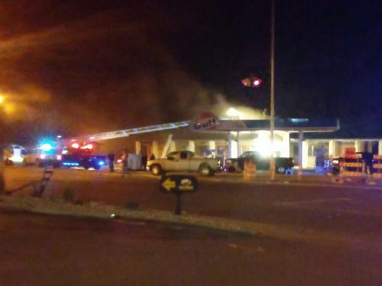 Firefighters try to put out the blaze early Sunday at the One Stop in Madison.