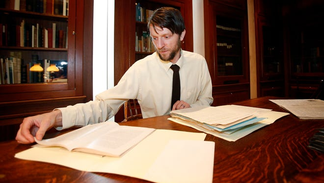 Elmira College archivist and curator Nathaniel Bell reads historical documents surrounding women's suffrage in Elmira.