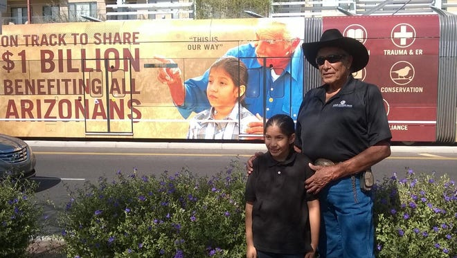 Gila River Indian Community Gov. Tom White and his granddaughter Sieana White stand in front of train with new light-rail wrap.