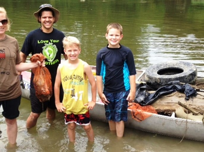 The Thomas family - Andrea, Paul, Zachary and Lance - use the grabber and orange garbage bags provided by Little Miami Inc. and River's Unlimited to help sweep the river clean Aug. 9 at Loveland Canoe & Kayak.