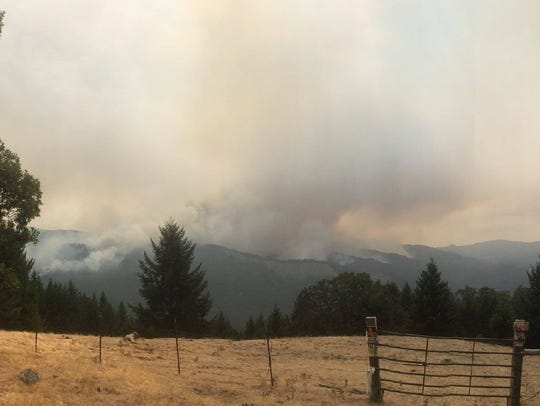 Smoke rises from the Chetco Bar Fire in southwestern