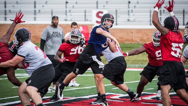 Ball State's Riley Neal runs through a drill with teammates during practice at Scheumann Stadium Thursday afternoon.