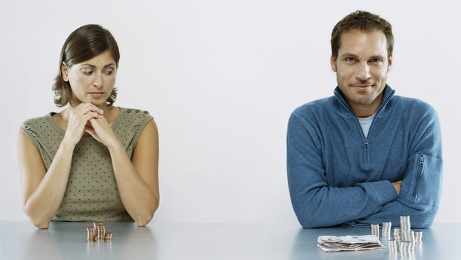 File photo shows man with more money sitting next to woman with less money.