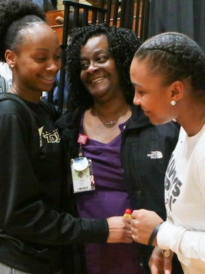 Anderson senior forward Jasmine Franklin (15), left, hugs her mother Ida Franklin, middle, near teammate Tamia Eatmon after a recent Trojans basketball game.