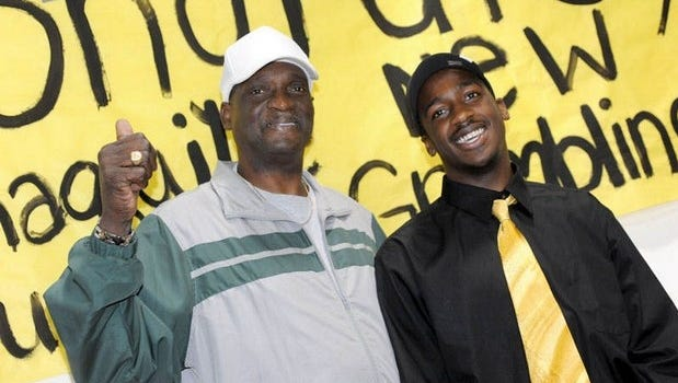 In this 2012 file photo, Shaquille Purifoy poses with his father Robert Gross on after signing a letter of intent to play football for Grambling State University.