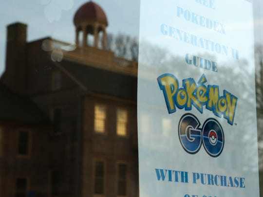 A business advertises a Pokemon GO promotion across from the New Castle Court House Museum in Old New Castle. Some city residents are at odds with the cellphone game that draws crowds to the city center.