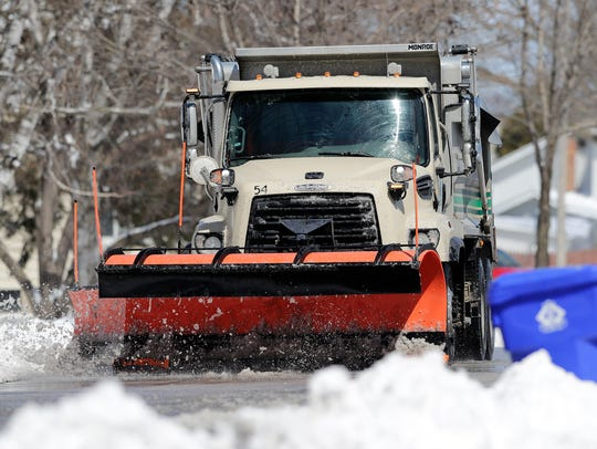 A snow plow clears streets after a snow storm on Wednesday,