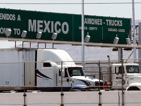 Trucks line up on the Bridge of the Americas to enter the U.S. on Tuesday. A trade pact will let armed U.S. agents speed cargo from Mexico.