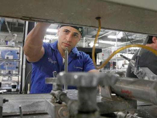 Spencerport's Otto Solano works at grinding and polishing down optics at Optimax Systems in Ontario, Wayne County.