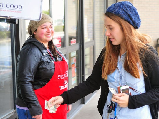 Chelsie Reid, of Las Cruces, donates money to the Salvation Army outside of Hobby Lobby on Friday. Volunteer Cristal Flores rings the bell for the organization's well-known Red Kettle Campaign.