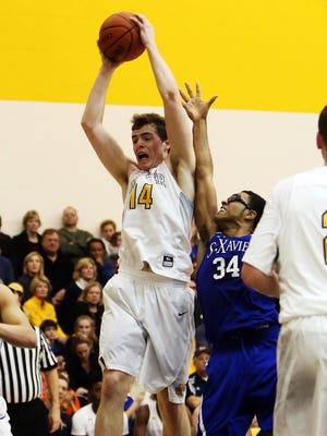 Moeller's Riley Voss grabs a rebound over St. Xavier's Blake Anderson.