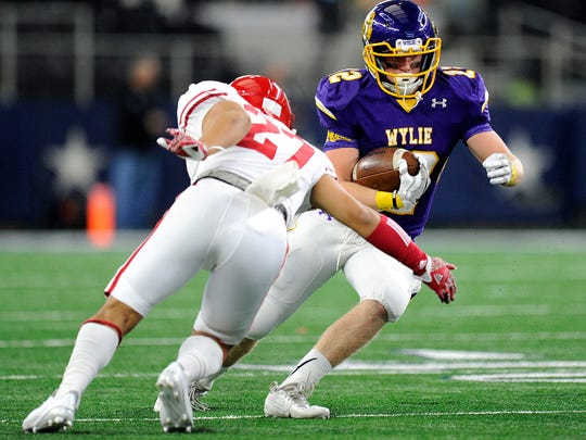 Wylie running back Brooks Pepper (12) tries to slips past Carthage linebacker Jose Dejulian (27) during the first quarter of Wylie's 31-17 loss in the Class 4A Div. I state championship game on Friday, Dec. 16, 2016, at AT&T Stadium in Arlington.