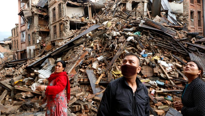 Family members look at a damaged buildings at Vhaktapur in Nepal on Monday, April 27. Sarah Sentz of Choteau, her boyfriend Ryan Edwards and friend Jennifer Thompson survived a devastating 7.8-magnitude earthquake that hit Nepal, where the three had been part of a trek.