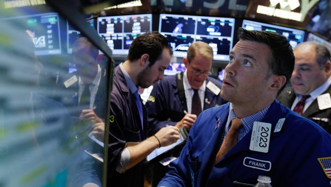 Specialist Frank Masiello (right) works with traders at his post on the floor of the New York Stock Exchange.